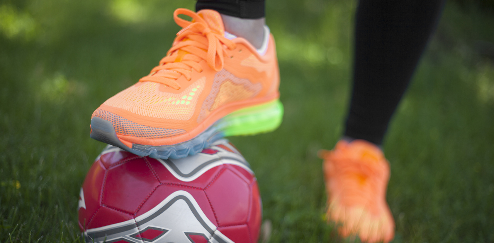 Foot wearing a bright orange shoe on soccer ball